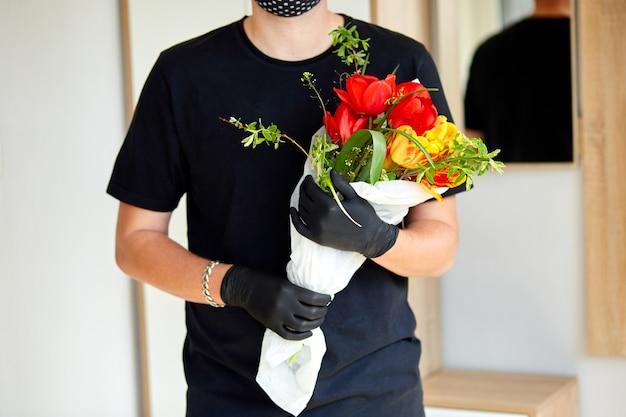 택배, 의료용 라텍스 장갑을 입은 배달원이 온라인 구매 꽃 꽃다발을 안전하게 배달합니다.