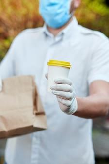 Курьер, курьер в защитной маске и медицинских перчатках доставляет еду на вынос и кофе. служба доставки в условиях карантина, вспышки заболевания, пандемии коронавируса ковид-19.