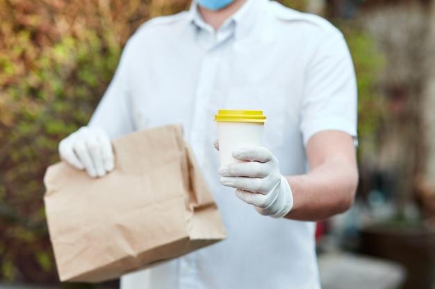 宅配便、防護マスクと医療用手袋の配達人が持ち帰り用の食品とコーヒーを配達します。