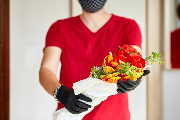 택배, 의료용 라텍스 장갑을 입은 빨간색 배달원은 코로나 바이러스가 유행하는 동안 온라인 구매 꽃 꽃다발을 안전하게 배달합니다. 집에있어 안전한 개념.