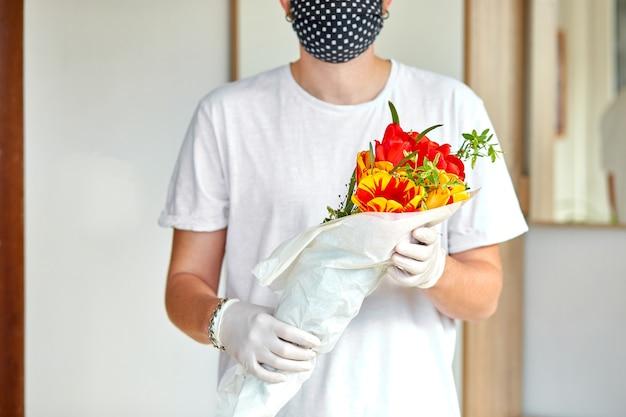 택배, 의료용 라텍스 장갑을 입은 흰색 배달원은 코로나 바이러스 전염병 동안 온라인 구매 꽃 꽃다발을 안전하게 배달합니다. 집에있어 안전한 개념.