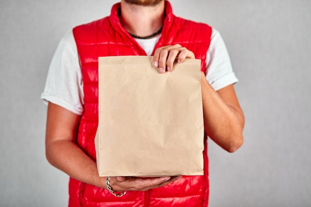 Courier, delivery man in red vest uniform delivers online purchases in brown paper bags