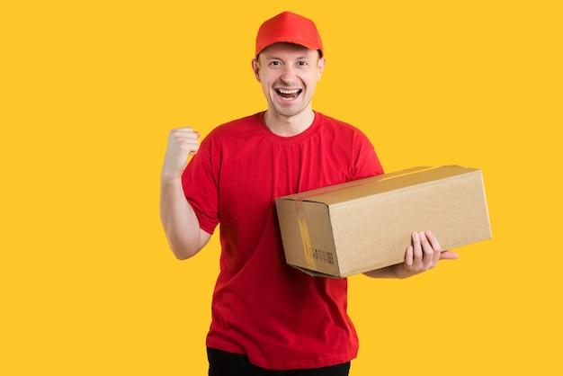 赤いユニフォームへの宅配便配達人は黄色の箱を持っています