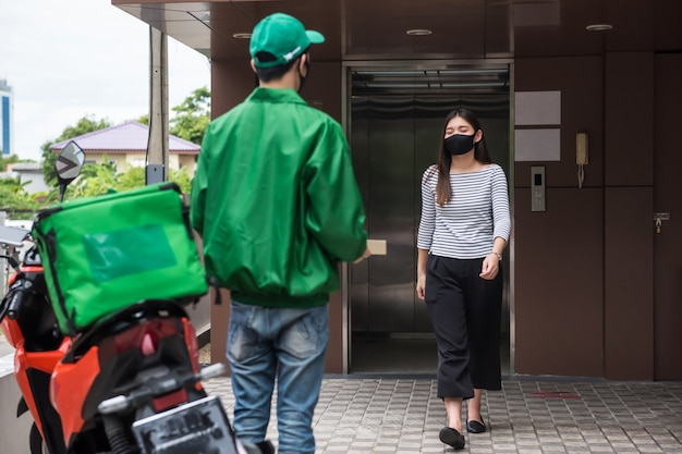 오토바이 등온 식품 상자 근처에서 제복을 입은 택배 배달원이 사무실이나 아파트에서 피자를 데리러 고객을 기다립니다. Covid-19 델타 기간 동안 가정이나 사무실 건물에 음식을 배달하는 새로운 표준입니다. 프리미엄 사진