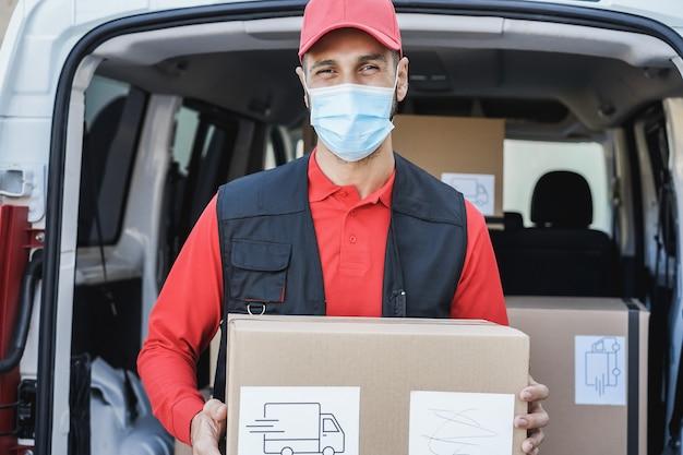 安全マスクを着用しながらパッケージを配達する宅配便の運転手男
