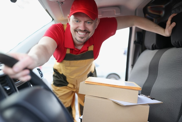 Courier driver picks up cardboard boxes in car
