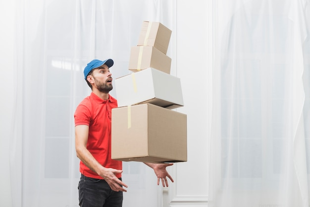 Courier dropping stack of parcels