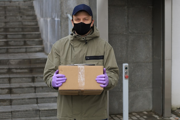 Courier in face mask and medicine gloves delivering parcel. coronavirus and quarantine concept.
