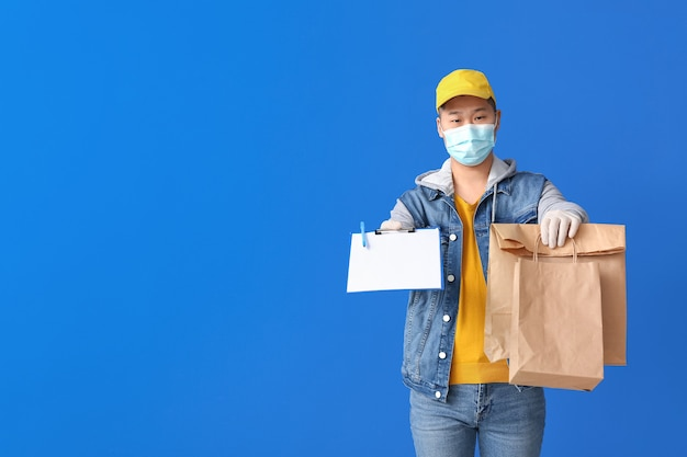 Courier of food delivery service on color surface