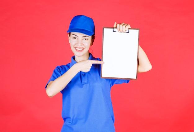 Ragazza del corriere in uniforme blu che tiene un tasklist.