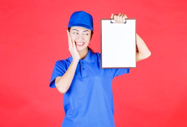 Курьерская девушка в синей форме держит список задач и выглядит задумчивой и смущенной.