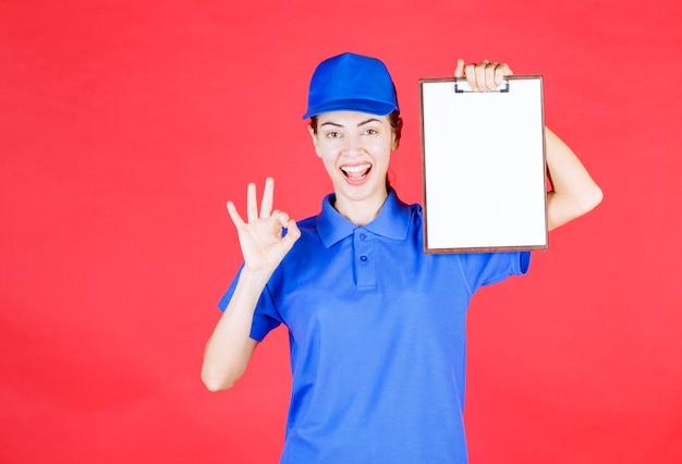 Курьер девушка в синей форме держит список задач и показывает знак удовольствия.