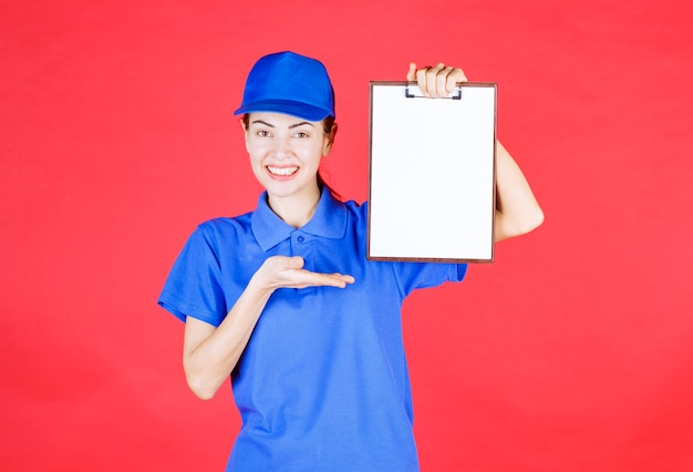Курьер девушка в синей форме держит список задач.