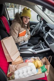 車の中で宅配便の女の子。フードデリバリーサービス。非接触型デリバリー、ボランティア