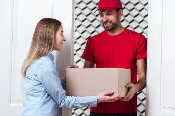 Courier giving the box to the client medium shot
