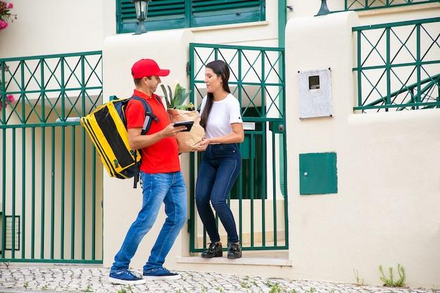 문에서 고객에게 종이 패키지를주는 택배. 태블릿 및 식료품가 게에서 음식을 가진 여자 회의 배달 남자. 배송 또는 배달 서비스 개념