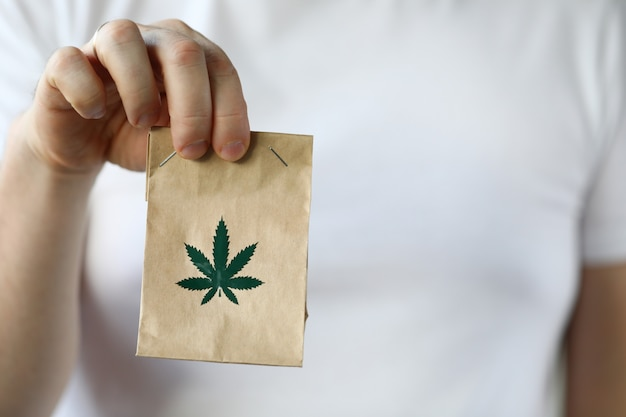 Courier hand passing package with marijuana