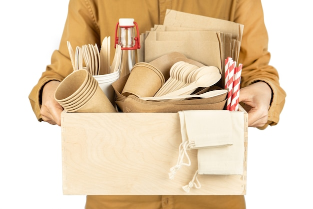 Courier holding a box with eco dishes for fast food and parasites isolated on a white background