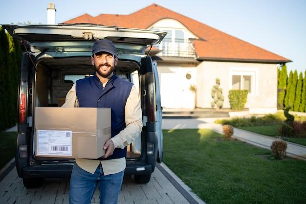 Курьер держит посылку и стоит у своего ва перед домом, готовый доставить.