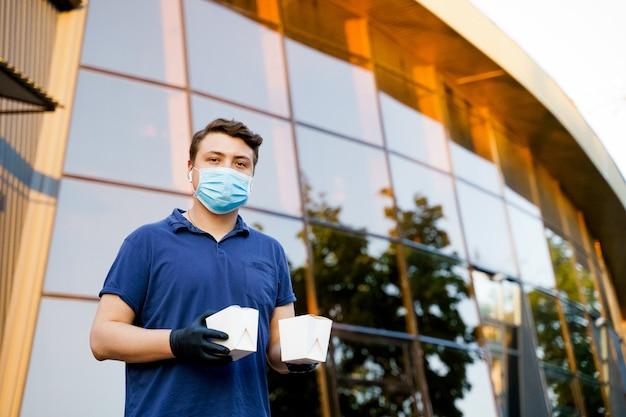 Courier는 의료용 장갑과 마스크로 일회용 식품 상자를 손에 들고 있습니다.