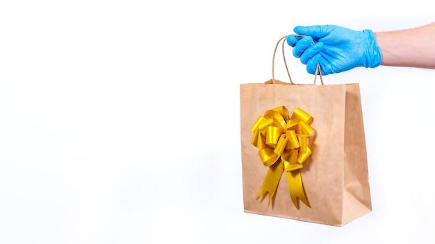 Курьер в синих перчатках держит подарочный пакет с золотым бантом