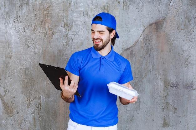 Курьер в синей форме держит пластиковую коробку для еды и читает список клиентов.