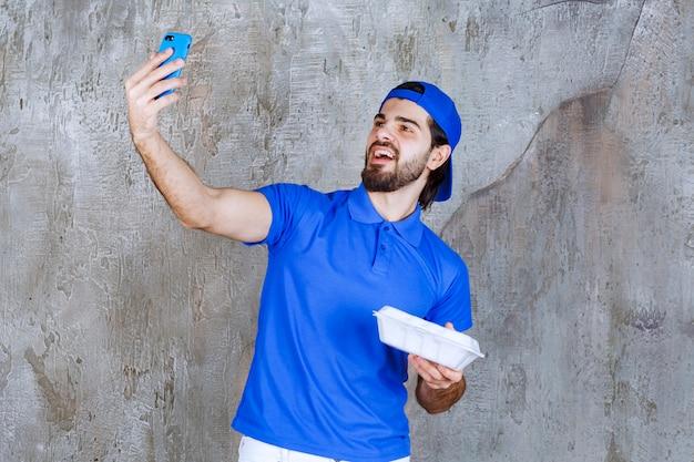 Курьер в синей форме держит пластиковую коробку для еды и принимает новые заказы по телефону