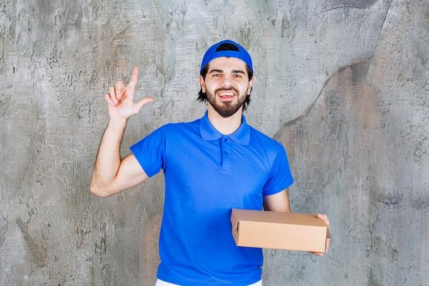 持ち帰り用の箱を持っている青い制服を着た宅配便業者は、混乱しているか、新しいアイデアを持っているように見えます。