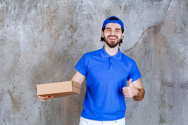 파란색 유니폼을 입은 택배는 테이크아웃 상자를 들고 긍정적인 손 기호를 보여줍니다.