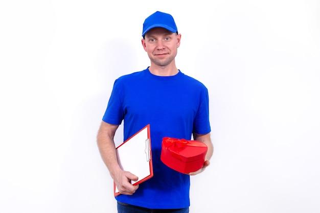 Курьер в синей форме держит красную подарочную коробку в форме сердца на день святого валентина. доставка на дом