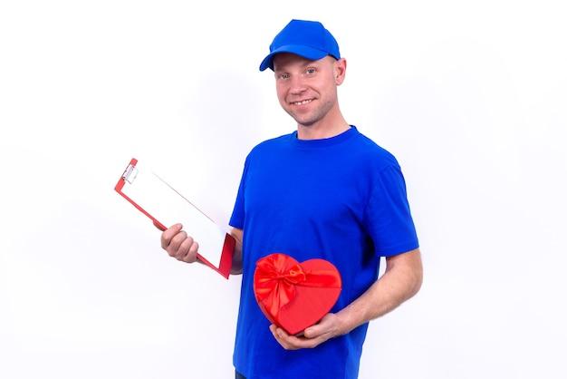 Курьер в синей форме держит подарочную коробку в форме красного сердца на день святого валентина.