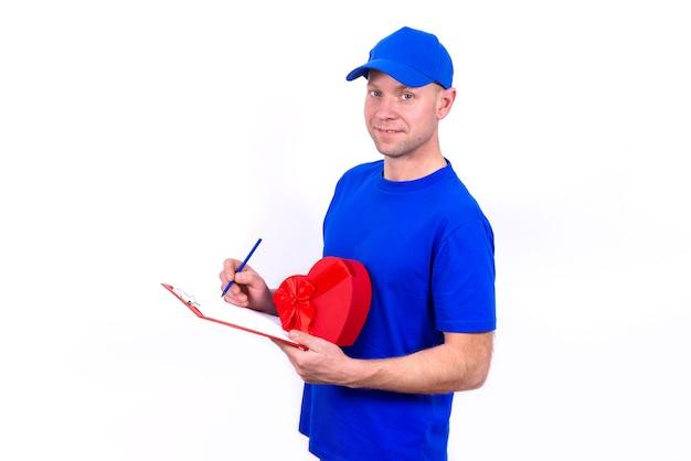 Курьер в синей форме держит красную подарочную коробку в форме сердца на день святого валентина и проверяет заказ на