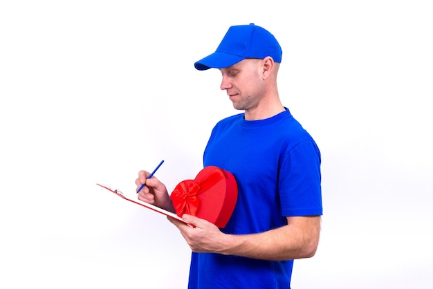 Курьер в синей форме держит красную подарочную коробку в форме сердца на день святого валентина.