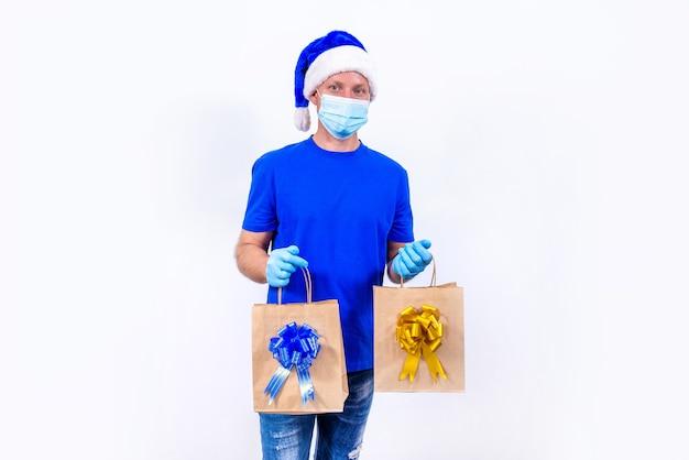 Курьер в синей форме, защитной медицинской маске, перчатках и шляпе санта-клауса держит подарочные пакеты