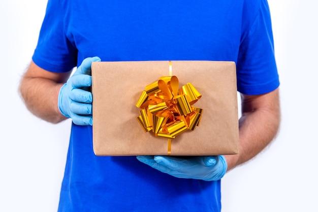 Курьер в синей форме, защитной медицинской маске, перчатках и шляпе санта-клауса держит подарочную коробку