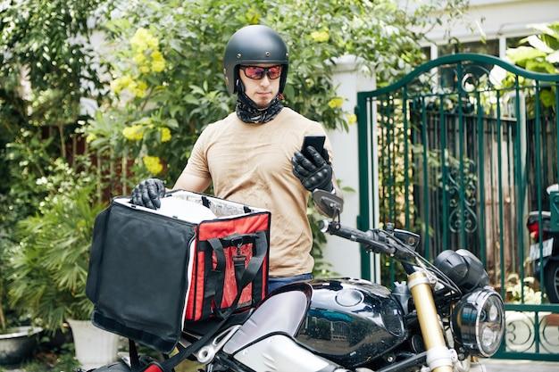 Курьер в каске и защитных очках принимает заказ из изолированной сумки и читает сообщение от ...