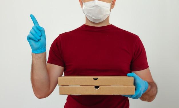 의료 장갑과 마스크의 택배는 피자 상자를 보유하고 있습니다. 검역 중 피자 배달. 서비스 격리 전염병 코로나 바이러스 독감 2019-ncov 개념.