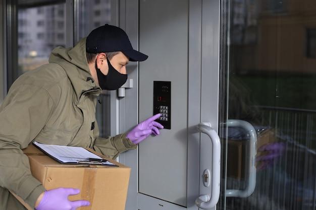 소포가 있는 약 마스크와 장갑을 낀 택배가 인터콤에 전화를 걸어 주문을 고객에게 전달합니다. 코로나바이러스와 격리 개념.
