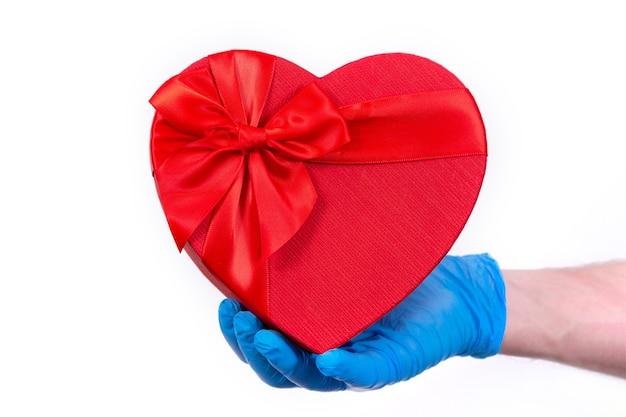 보호 장갑의 택배는 발렌타인 데이를위한 빨간 하트 모양의 선물 상자를 보유하고 있습니다.