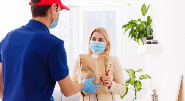 Курьер в защитной маске и медицинских перчатках доставляет еду на вынос. служба доставки в условиях карантина, вспышки заболевания, пандемии коронавируса covid-19.