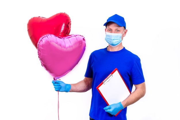 Курьер в защитной маске, перчатках держит красную подарочную коробку в форме сердца и воздушный шар на день святого валентина.