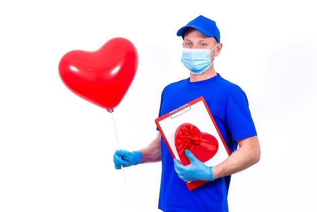 Курьер в защитной маске, перчатках держит красную подарочную коробку в форме сердца и воздушный шар на день святого валентина