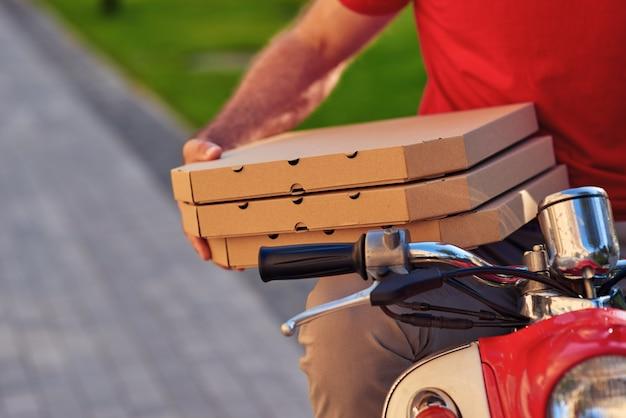 Курьер в красной форме сидит на скутере и держит коробки для пиццы, выборочный фокус. концепция доставки еды