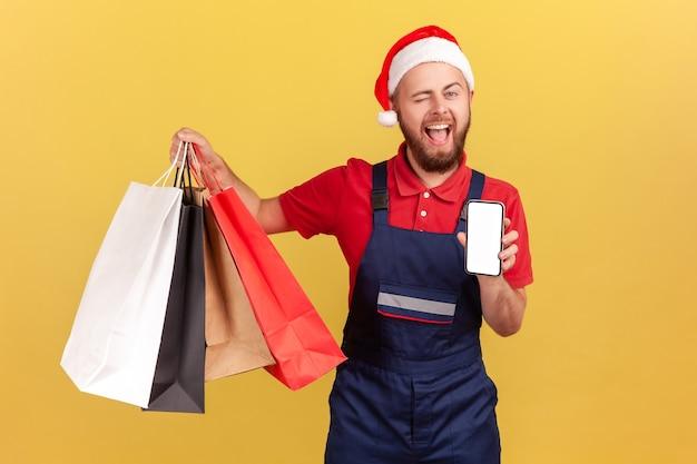 Курьер в шляпе санта-клауса держит сумки и смартфон с пустым дисплеем