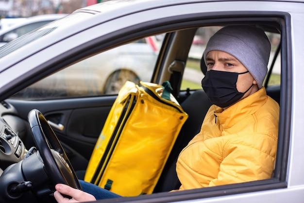 黒の医療用マスクを備えた車内の宅配便、座席に配達用バックパック。フードデリバリーサービス