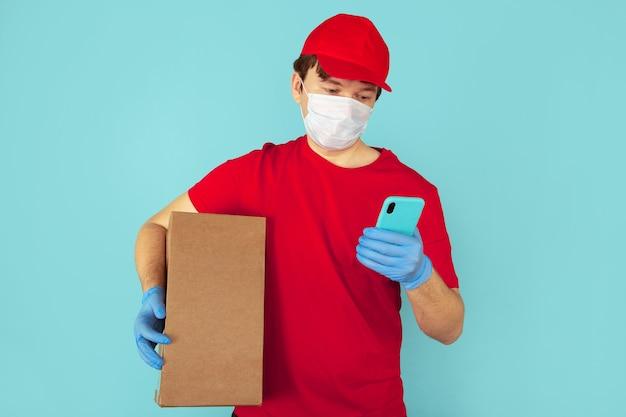Курьер в красной одежде держит большую коробку и пользуется телефоном в синем футляре.