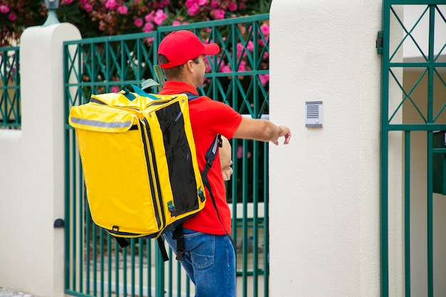 등온 음식 배낭과 패키지 울리는 초인종과 제복을 입은 택배. 배송 또는 배달 서비스 개념