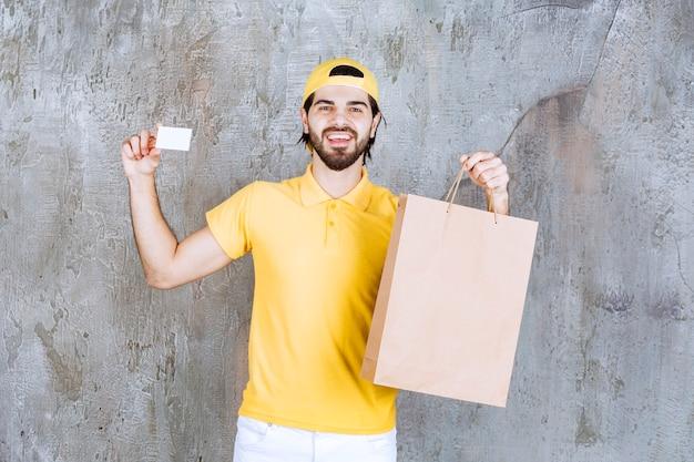 Курьер в желтой форме держит картонную сумку для покупок и показывает свою визитную карточку