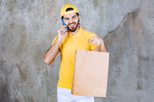 Курьер в желтой форме держит картонную сумку для покупок и разговаривает по телефону