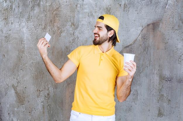 使い捨てカップを持って名刺を紹介する黄色い制服の宅配便。